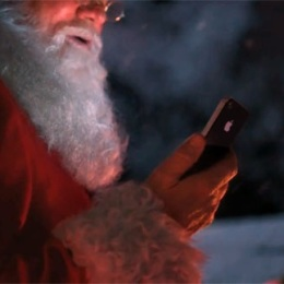 Santa Claus listening to Christmas jingles on Phone